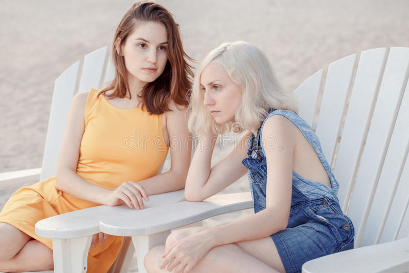 Portret van twee peinzende droevige witte Kaukasische unformal jonge vrienden van meisjes hipster studenten buiten op de strandzo stock afbeelding