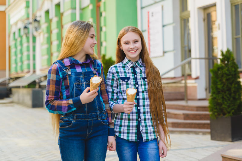 Portret van twee tienermeisjes die bevinden zich etend samen roomijs stock foto's
