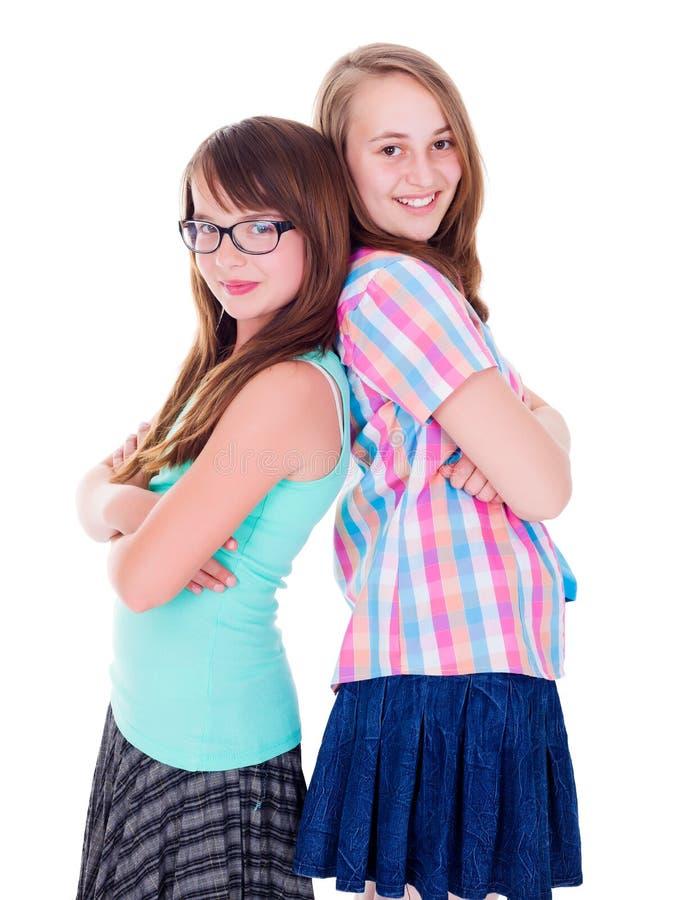 Portret van twee tienermeisjes die zich rijtjes bevinden stock foto's
