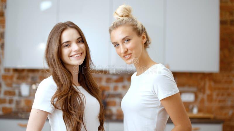 Portret van twee vrolijke tienermeisjes die camera en het glimlachen bekijken stock afbeelding