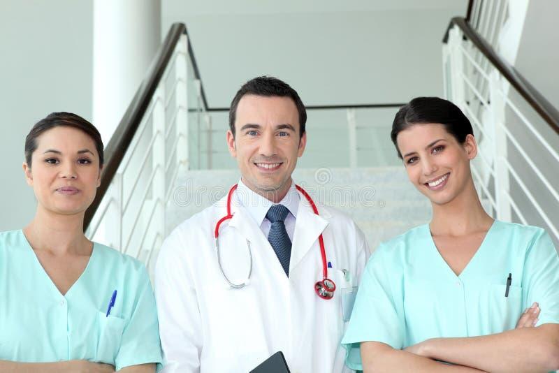 Vrouwelijke verpleegsters met arts stock afbeeldingen