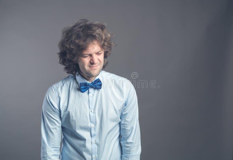 Portret van uitgeputte droevige kerel met ruwharig haar die en zich met apathie terugtrekken kijken Geïsoleerd op grijze achtergr stock afbeeldingen