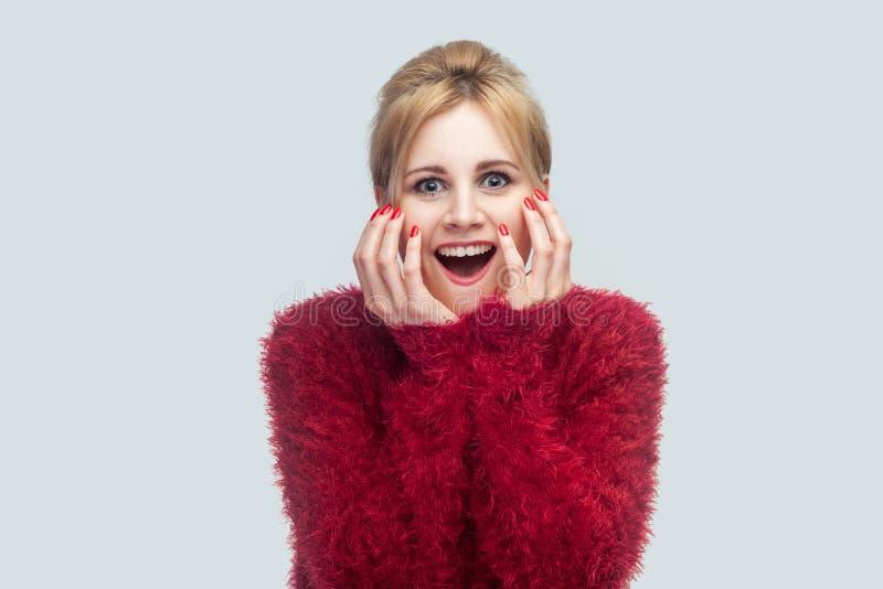 Portret van verbaasde mooie jonge blonde vrouw in rode blouse die en zich camera met verrast gezicht en geluknieuws bevinden beki stock fotografie