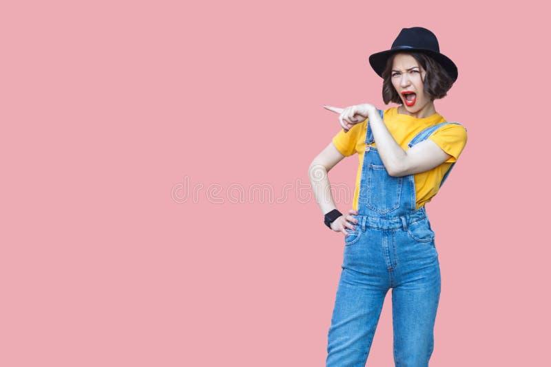 Portret van verbaasde mooie jonge vrouw in gele t-shirt en blauwe denimoverall met make-up en zwarte en hoed die bevinden zich ri stock fotografie