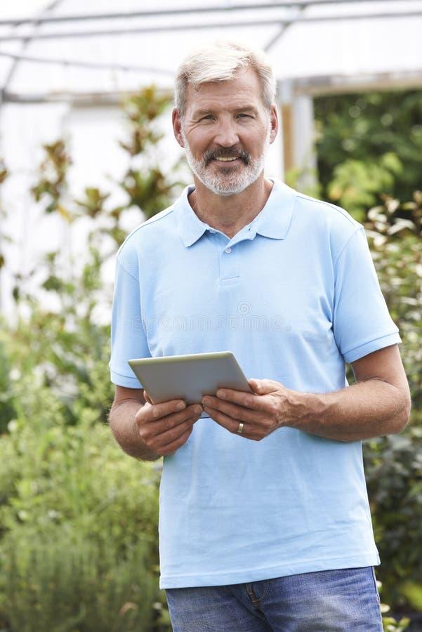 Portret van Verkoopmedewerker in Tuincentrum met Digitale Tablet royalty-vrije stock afbeelding