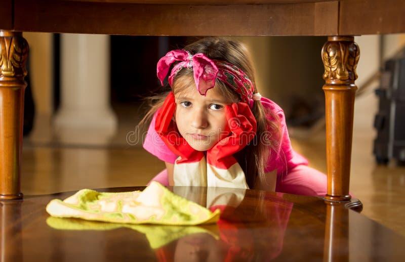 Portret van vermoeid droevig meisje die houten lijst schoonmaken stock afbeeldingen