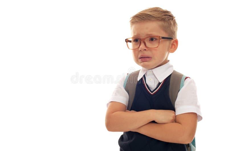 Portret van vermoeide droevige de schooljongen van ANS met oogglazen en rugzak stock afbeelding
