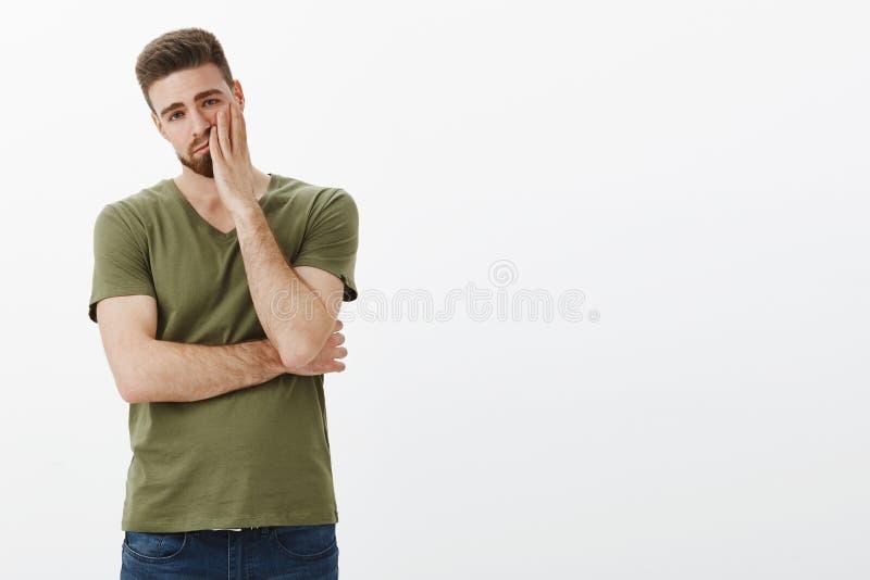 Portret van vermoeide en onverschillige knappe vriend die tijdens argument facepalming worden hersenspoeld die uitgeput kijken en stock afbeelding