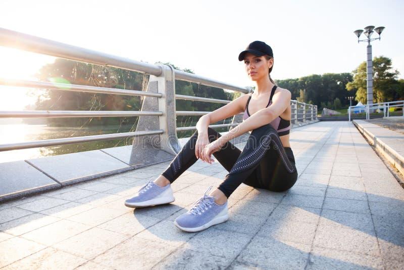Portret van vermoeide geschiktheids jonge vrouw in openlucht in de stad Jonge vrouwenagent die na trainingzitting op zonnig ruste stock afbeelding