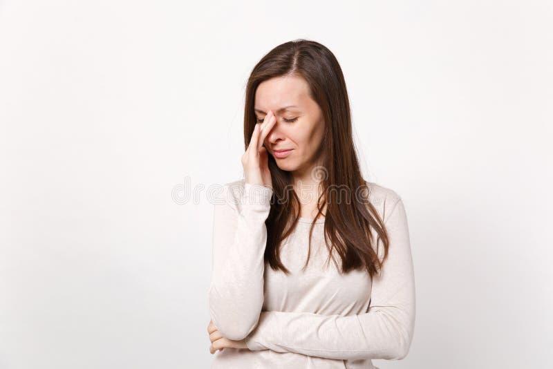Portret van vermoeide schreeuwende ontevreden jonge vrouw in lichte kleren die scheuren met hand afvegen die op witte muur wordt  royalty-vrije stock afbeeldingen