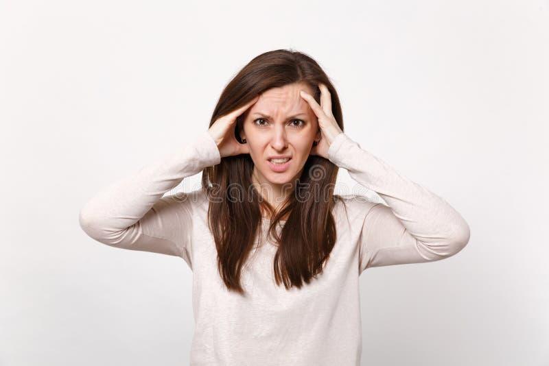 Portret van vermoeide uitgeputte jonge vrouw die in lichte kleren hand op hoofd zetten die camera geïsoleerd op witte muur kijken royalty-vrije stock afbeeldingen