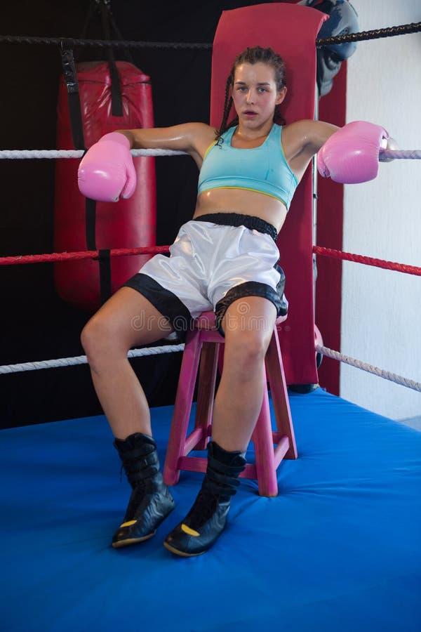 Portret van vermoeide vrouwelijke bokserzitting op kruk bij hoek stock afbeeldingen