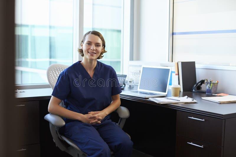 Portret van Verpleegster Wearing Scrubs Sitting bij Bureau in Bureau stock foto's