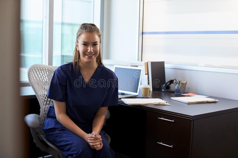 Portret van Verpleegster Wearing Scrubs Sitting bij Bureau in Bureau stock fotografie