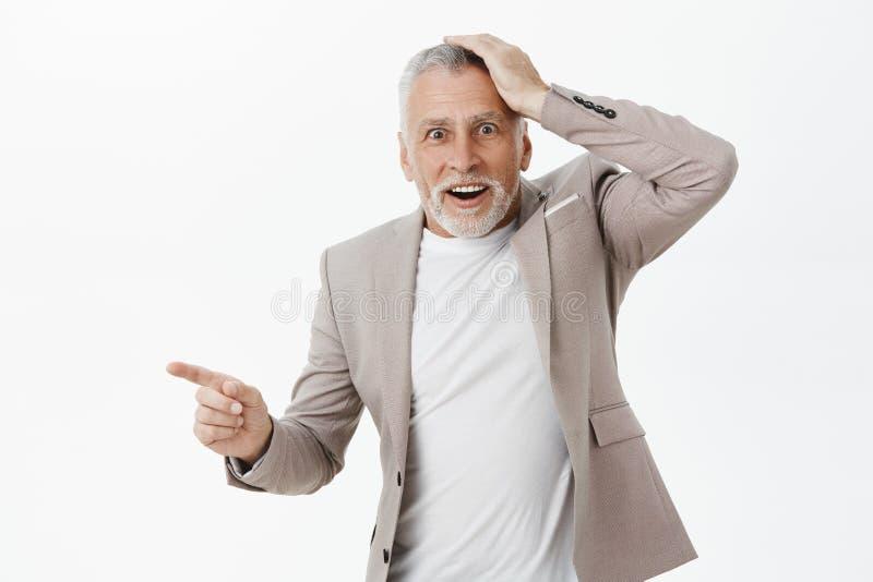 Portret van verraste hogere en geïmponeerde vader die houdend hand op hoofd van verrassing en verbazing het richten worden verbaa stock fotografie