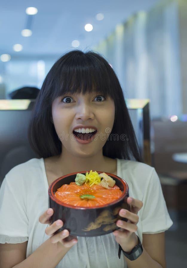 Portret van verraste jonge Aziatische vrouw die Japanse voedselschotel houden stock fotografie