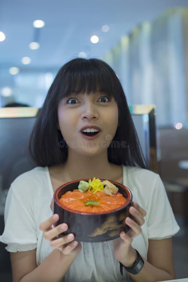 Portret van verraste jonge Aziatische vrouw die Japanse voedselschotel houden royalty-vrije stock foto