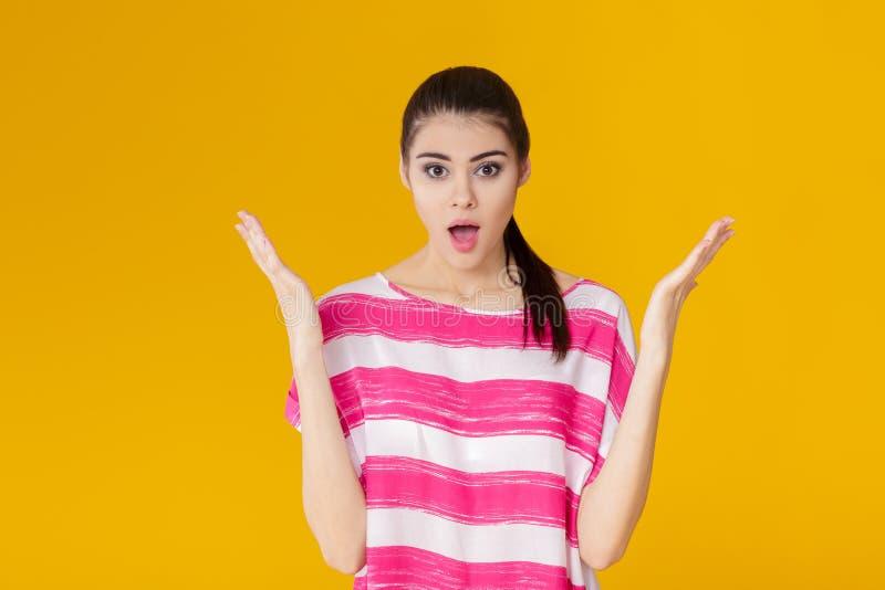 Portret van verraste jonge donkerbruine vrouw in roze overhemd op gele achtergrond Het meisje bekijkt camera royalty-vrije stock foto's