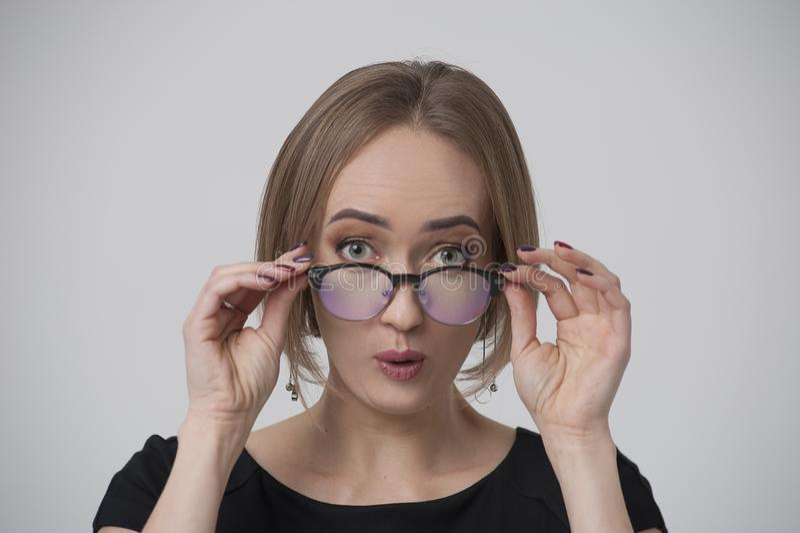 Portret van verraste jonge vrouw in modieuze bril stock fotografie