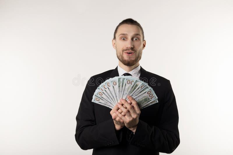Portret van verraste knappe zakenman die zwart kostuum dragen die geldbankbiljetten tonen royalty-vrije stock afbeeldingen