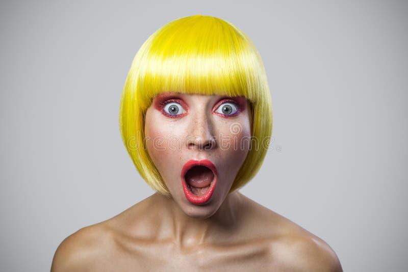 Portret van verraste leuke jonge vrouw met sproeten, rode make-up en gele pruik, die camera met verbaasd wonder gezicht bekijken stock foto