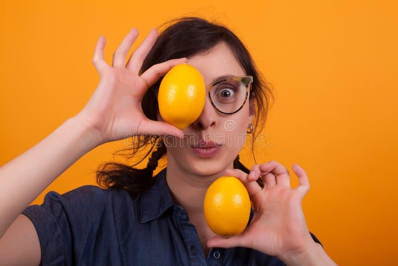 Portret van verraste mooie vrouw met twee smakelijke sinaasappelen als ogen over gele achtergrond royalty-vrije stock afbeeldingen