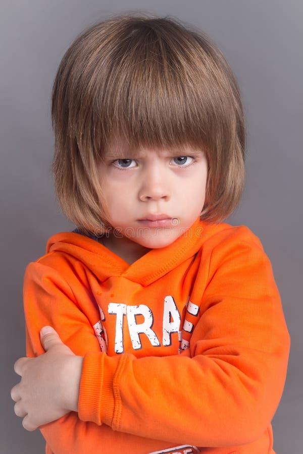 Portret van verstoorde leuk weinig jongen in sinaasappel hoodie stock fotografie