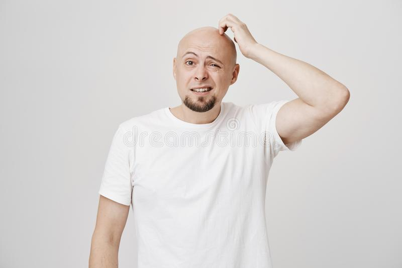 Portret van verward kaal Kaukasisch mannelijk model met stomme uitdrukking, hoofd krassen en het kijken opzij hebbend geen royalty-vrije stock foto's