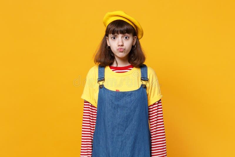 Portret van verwarde leuke meisjestiener in Franse baret en denim sundress blazende die lippen op gele muur worden geïsoleerd stock afbeelding