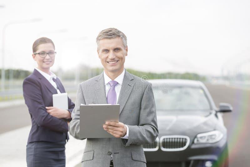 Portret van verzekeringsagent met klembord die zich tegen onderneemster door analyseauto bevinden royalty-vrije stock afbeeldingen