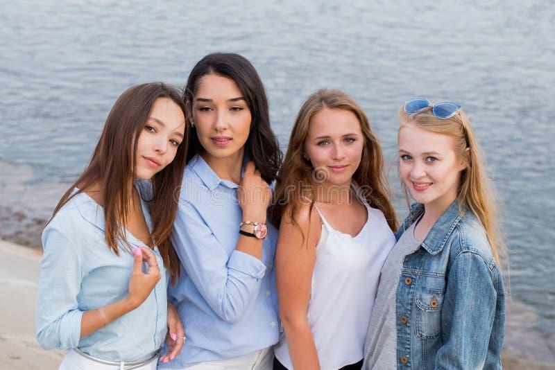 Portret van vier femlevrienden die vriendschappelijk camera, gelukkige glimlach bekijken, mensen, levensstijl, vriendschapsconcep stock foto's