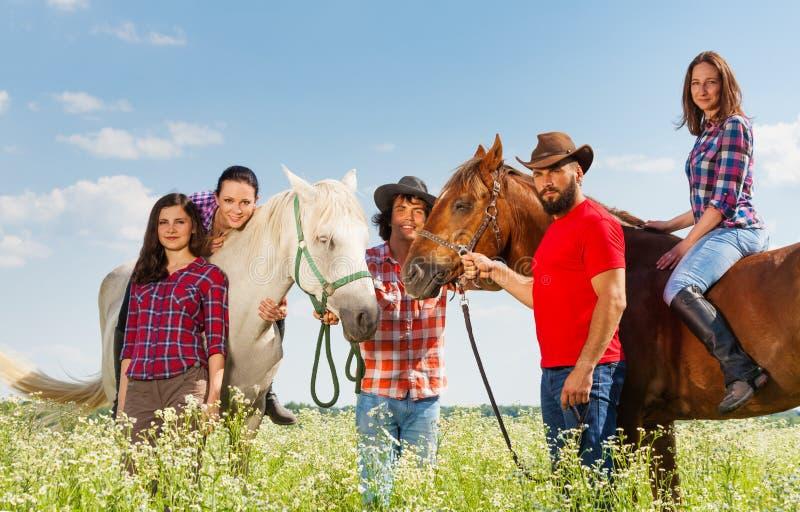 Portret van vijf gelukkige jonge horseback ruiters stock afbeeldingen