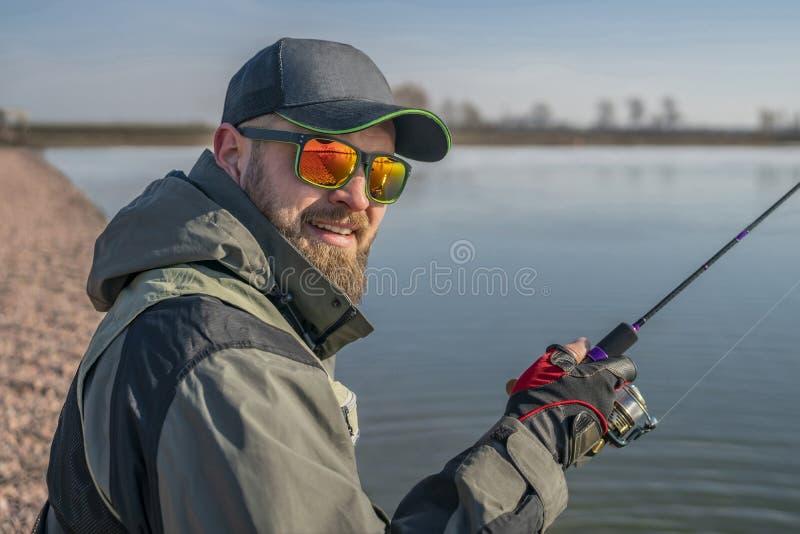 Portret van visser De gebaarde mens in GLB en zonnebril houdt hengel bij meer stock afbeelding