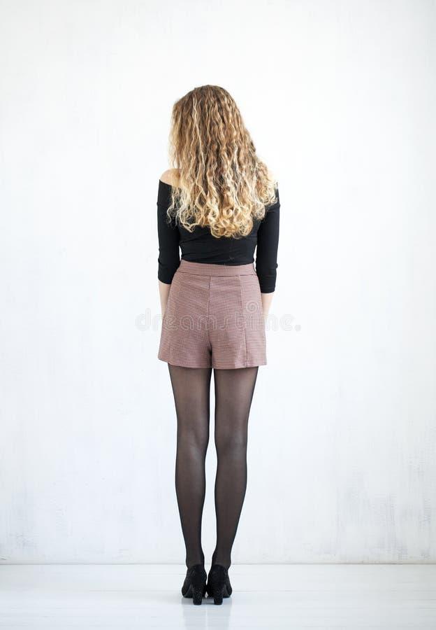 Portret van volledig lengte krullend blonde in een zwarte blouse en een korte rok royalty-vrije stock fotografie