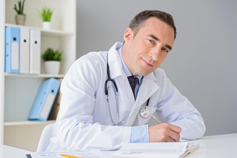 Portret van volwassen artsenzitting bij zijn bureau stock foto's