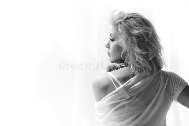 Portret van volwassen blondevrouw die venster bekijken stock foto's