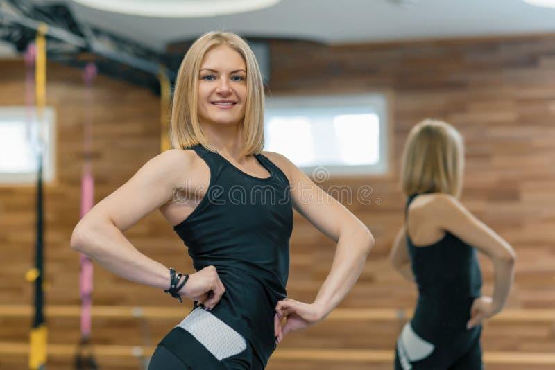 Portret van volwassen de vrouwen persoonlijke trainer van de blondegeschiktheid in gymnastiek, mooi glimlachend wijfje die in cam stock fotografie