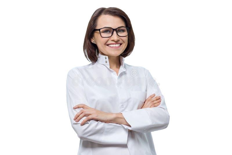 Portret van volwassen glimlachende vrouwelijke cosmetologist arts met gekruiste wapens, witte geïsoleerde achtergrond, stock afbeelding