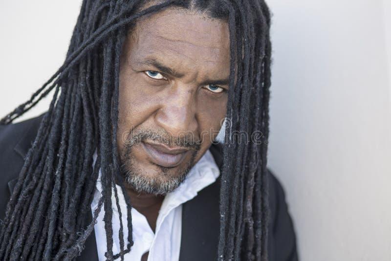 Portret van volwassen sterke zwarte mensen met lang dreadlocks en blauwe ogen stock afbeelding