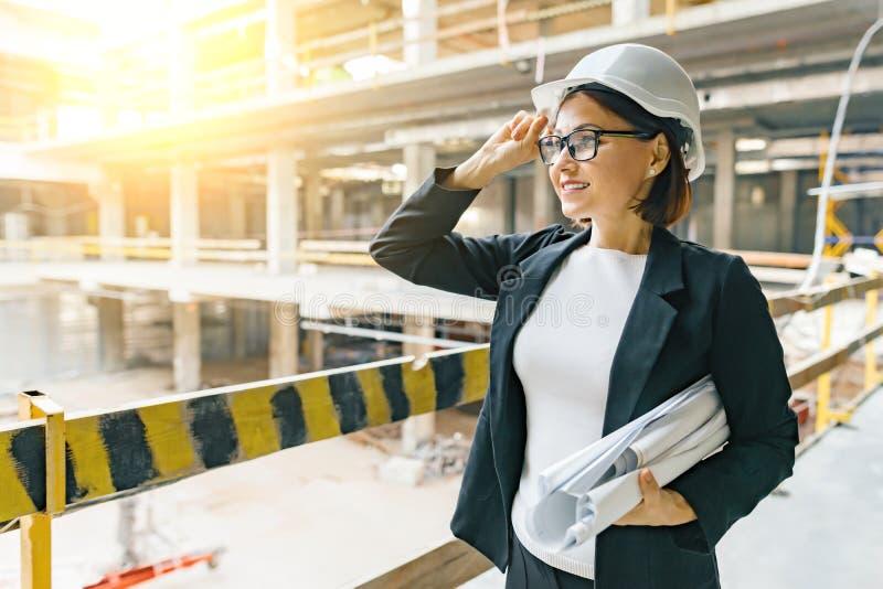 Portret van volwassen vrouwelijke bouwer, ingenieur, architect, inspecteur, manager bij bouwwerf Vrouw met plan, die bekijken stock foto's