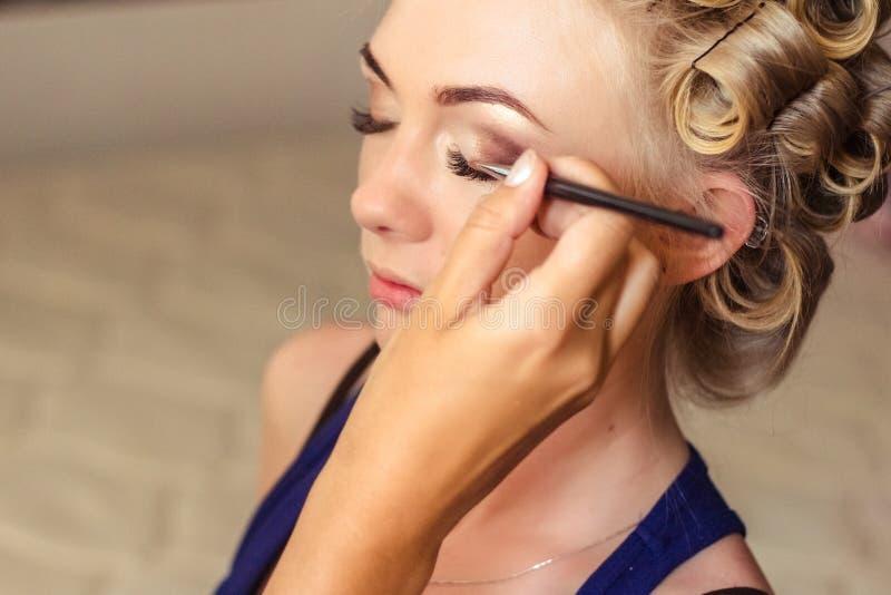 Portret van voorbereiding van jonge vrouw met make-upkunstenaar royalty-vrije stock afbeelding