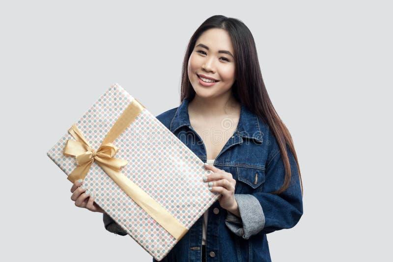 Portret van vriendelijkheids aantrekkelijk jong Aziatisch meisje in blauw denimjasje die en met gele boog en toothy smil huidig b stock fotografie