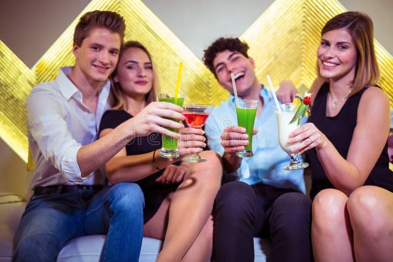 Portret van vrienden die van cocktail in nachtclub genieten stock afbeeldingen