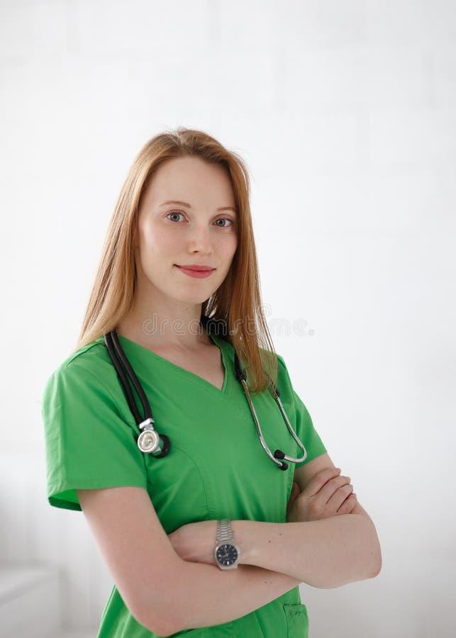 Portret van vriendschappelijke, glimlachende vrouwelijke arts, beroepsbeoefenaar met groene laboratoriumlaag Natuurlijke lichte p royalty-vrije stock foto's