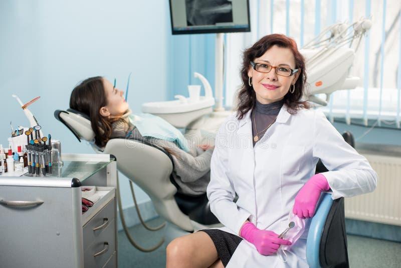 Portret van vriendschappelijke vrouwentandarts met patiënt in het tandbureau tandheelkunde royalty-vrije stock afbeelding