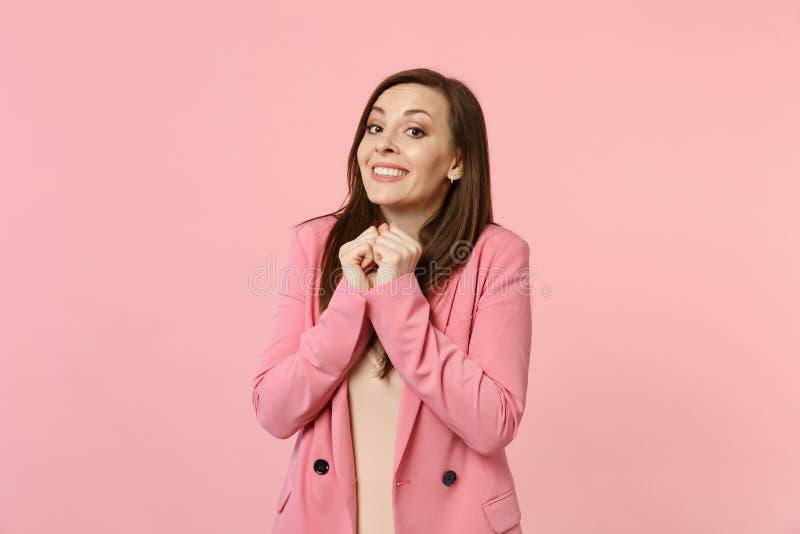 Portret van vrij glimlachende aantrekkelijke jonge vrouw die in die jasje vuisten dichtklemmen dichtbij gezicht op pastelkleur ro royalty-vrije stock foto
