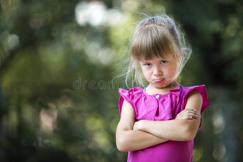 Portret van vrij grappig humeurig ongelukkig jong blond kindmeisje die in roze sleeveless kleding boos en unsatisfied op vaag voe royalty-vrije stock foto
