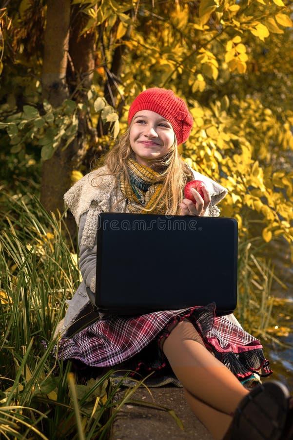 Portret van vrij jong meisje die in rode hoed een appel en het glimlachen eten stock foto