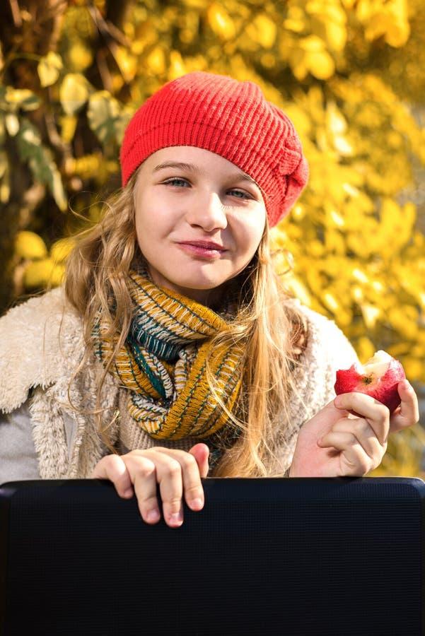 Portret van vrij jong meisje die in rode hoed een appel en het glimlachen eten royalty-vrije stock fotografie
