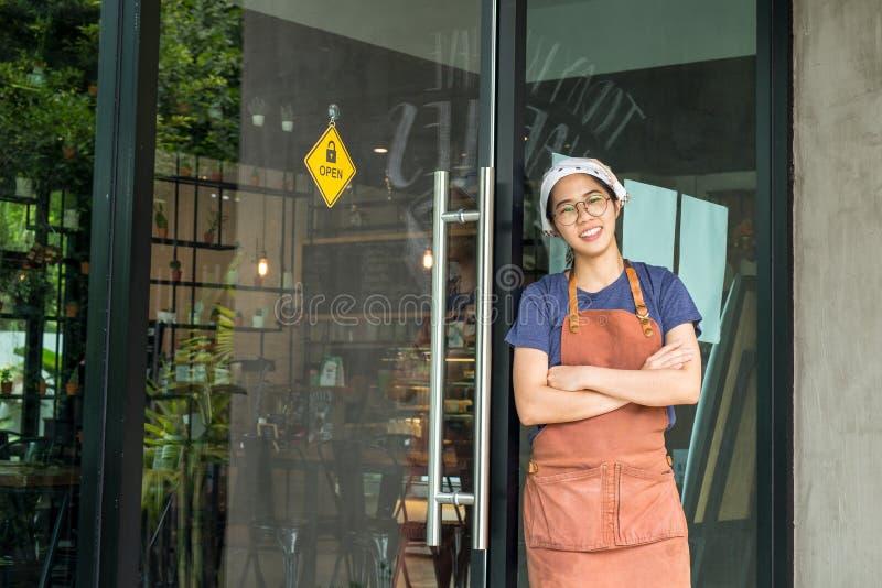 Portret van vrij jonge serveerster bevindende die wapens in koffie worden gekruist stock fotografie